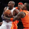 Photo - Los Angeles Lakers guard Kobe Bryant, left, is fouled by New York Knicks guard J.R. Smith, right, as forward Carmelo Anthony, center, watches during the first half of their NBA basketball game in Los Angeles, Tuesday, Dec. 25, 2012. (AP Photo/Alex Gallardo)