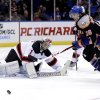 New Jersey Devils goalie Johan Hedberg, left, watches as New York Islanders\' Matt Moulson tries to recover the puck during the second period of the NHL hockey game on Sunday, Feb. 3, 2013, in Uniondale, N.Y. (AP Photo/Seth Wenig)