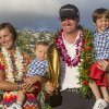 Photo - Jimmy Walker, second from right, holds his son Mclain, right, as his wife Erin Walker, left, holds their son Beckett, while they pose for pictures with the Sony Open Trophy after Jimmy won the golf tournament at Waialae Country Club, Sunday, Jan. 12, 2014, in Honolulu. (AP Photo/Eugene Tanner)