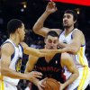 Toronto Raptors\' Jonas Valanciunas, center, drives for the basket as Golden State Warriors\' Stephen Curry, left, and Andrew Bogut defend during the first half of an NBA basketball game in Oakland, Calif., Monday, March 4, 2013. (AP Photo/George Nikitin)
