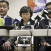Serim Han, center, holds a picture of her husband Ki-Suck Han, as she is flanked by New York City Comptroller John Liu, left, and Rev. Won Tae Cho, Han\'s pastor, during a news conference on Wednesday, Dec. 5, 2012 in New York. A homeless man was arrested Wednesday in the death of Ki-Suck Han, who was pushed onto the tracks and photographed just before a train struck him. (AP Photo/Bebeto Matthews)