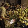 Man places a flower tribute at the Dutch embassy to commemorate victims of Malaysia Airlines plane crash in Kiev, Ukraine, Thursday, July 17, 2014. A Malaysian Airlines passenger jet was shot down in eastern Ukraine on Thursday, and both the Ukrainian government and pro-Russian rebels blamed one another for the attack. (AP Photo/Sergei Chuzavkov)
