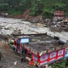 Photo -   People gather to watch river water that washed away a bridge as a flash flood strikes in Uttarkashi district, India, Saturday, Aug. 4, 2012. Flash floods and landslides triggered by torrential rains killed people in northern India, including firefighters who were swept away as they helped rescue the stranded, an official said Saturday. (AP Photo)