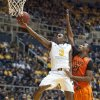 Photo - West Virginia's Juwan Staten, left, drives past Oklahoma State's Kamari Murphy during the second half of an NCAA college basketball game Saturday, Jan. 11, 2014, in Morgantown, W.Va. Oklahoma State won 73-72. (AP Photo/Andrew Ferguson)