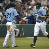 Photo - Tampa Bay Rays' Evan Longoria, right, is congratulated by teammate Matt Joyce (20) after hitting a solo home run during the sixth inning of a baseball game against the New York Yankees in St. Petersburg, Fla., Sunday, Aug. 25, 2013. (AP Photo/Phelan M. Ebenhack)