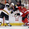 Ottawa Senators\' Chris Neil (25) and Boston Bruins\' Aran Johnson (45) fight for possession of the puck during the first period of their NHL hockey game, Thursday, March 21, 2013, in Ottawa, Ontario. (AP Photo/The Canadian Press, Fred Chartrand)