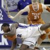 Photo - TCU forward Devonta Abron (23) loses his footing in front of Texas forward Connor Lammert (21) during the first half of an NCAA college basketball game Tuesday, Feb. 19, 2013, in Fort Worth, Texas. (AP Photo/LM Otero)