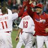 Photo - Philadelphia Phillies' Jimmy Rollins, left, gets a high-five from bench coach Larry Bowa, right, after hitting a solo home  in the tenth inning to win a baseball game against the Miami Marlins, Saturday, April 12, 2014, in Philadelphia. The Phillies won 5-4. (AP Photo/Tom Mihalek)