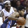 Miami Heat\'s LeBron James, left, blocks Charlotte Bobcats\' Chris Douglas-Robert (55) during the second half of an NBA basketball game in Miami, Monday, March 3, 2014. LeBron James scored a team recond of 61 points. The Heat won 124-107. (AP Photo/J Pat Carter)