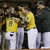 Photo - Oakland Athletics' Jed Lowrie (8) celebrates with teammates in the dugout after hitting a three-run home run against the Minnesota Twins during the sixth inning of a baseball game on Thursday, Sept. 19, 2013, in Oakland, Calif. (AP Photo/Marcio Jose Sanchez)