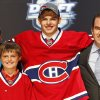 Photo -   Alex Galchenyuk, center, smiles with officials from the Montreal Canadiens after being chosen third overall in the first round of the NHL hockey draft on Friday, June 22, 2012, in Pittsburgh. (AP Photo/Keith Srakocic)