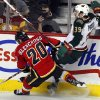 Minnesota Wild\'s Nate Prosser, right, gets checked by Calgary Flames\' Curtis Glencross during the first period of their NHL hockey game, Monday, Feb. 11, 2013, in Calgary, Alberta. (AP Photo/The Canadian Press, Jeff McIntosh)