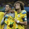 Photo - Brazil's David Luiz, right, and goalkeeper Julio Cesar hold up the team jersey of injured Brazilian star Neymar as they sing the anthem before the World Cup semifinal soccer match between Brazil and Germany at the Mineirao Stadium in Belo Horizonte, Brazil, Tuesday, July 8, 2014. (AP Photo/Matthias Schrader)