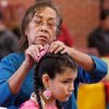 Francelina Roy, a Kiowa, places a colorful headpiece into the hair of her granddaughter, Stephanie Tongkeamha, 10, who is Ponca and Kiowa. She performed cloth dances with a sister and a cousin. At least 500 people representing several dozen Native American Nations within the state attended a New Year\'s pow-wow in the Centennial Building at State Fair Park Saturday , January 7, 2012, The celebration started around shortly after noon and continued into the night. Several hundred took part in the various dancers and the dancers wore tribal regalia. Photo by Jim Beckel, The Oklahoman