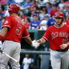 Photo - Los Angeles Angels' Chris Iannetta (17) is congratulated by Albert Pujols after scoring a run on a sacrifice fly by Mike Trout against the Texas Rangers during the third inning of a baseball game, Friday, Aug. 15, 2014, in Arlington, Texas. (AP Photo/Jim Cowsert)