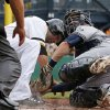 Photo - Pittsburgh Pirates' Neil Walker, center, is tagged out by Milwaukee Brewers catcher Jonathan Lucroy during the second inning of a baseball game in Pittsburgh Sunday, June 8, 2014. Walker was attempting to score from third on a single to right field by Pirate's Gaby Sanchez. (AP Photo/Gene J. Puskar)