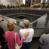 Family members of those who died in the Sept. 11, 2001 World Trade Center attacks, gather at the edge of the north reflecting pool of the Sept. 11 memorial during 10th anniversary ceremonies at the site, in New York, Sunday Sept. 11, 2011. (AP Photo/Chip Somodevilla, Pool)
