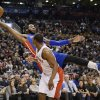 Photo - Detroit Pistons center Andre Drummond, top, lunges backward out of bounds to keep a ball in play as Toronto Raptors guard Kyle Lowry looks on during first-half NBA basketball game action in Toronto, Wednesday, Jan. 8, 2014. (AP Photo/The Canadian Press, Frank Gunn)