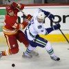 Photo - Vancouver Canucks' Christopher Tanev, right, battles for the puck with Calgary Flames' Steve Begin during first period NHL action in Calgary on Sunday, March 3, 2013. (AP Photo/The Canadian Press, Larry MacDougal)