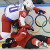 Photo - Anna Shibanova of Russia and Lara Stalder of Switzerland collide during the 2014 Winter Olympics women's ice hockey quarterfinal game at Shayba Arena, Saturday, Feb. 15, 2014, in Sochi, Russia. (AP Photo/Matt Slocum)
