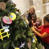 Foreground to background, kindergarten students Syanne McKaufman, Camryn Rodriquez-Stone, Avery O'Neal and St. James Catholic Principal Anne Codding decorate the school's Jesse tree displayed near the altar at St. James the Greater Catholic Church. Photos by Jim Beckel, THE OKLAHOMAN