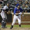 Atlanta Braves catcher Gerald Laird, left, joins New York Mets\' Ike Davis as they watch Davis\'s eighth-inning, two-run, single in the Mets 4-2 victory during a baseball game at Citi Field in New York, Sunday, May 26, 2013. (AP Photo/Kathy Willens)