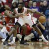 Photo - Milwaukee Bucks' Brandon Knight, left, falls backward after making contact with Houston Rockets' James Harden (13) during the first quarter of an NBA basketball game, Saturday, Jan. 18, 2014, in Houston. Knight was called for a foul. (AP Photo/David J. Phillip)