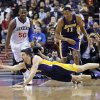 Photo - Los Angeles Lakers' Ryan Kelly, bottom, dives for a loose ball in front of Wesley Johnson (11) and Philadelphia 76ers' Lavoy Allen (50) during the first half of an NBA basketball game on Friday, Feb. 7, 2014, in Philadelphia. (AP Photo/Michael Perez)