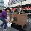 Lakers fan Jeannette Hernandez, lays a flower at the statue of the late Laker announcer Chick Hearn for Lakers\' owner Jerry Buss at the Staples Center in downtown Los Angeles on Monday Feb. 18,2013. Buss, the Los Angeles Lakers\' owner who shepherded the NBA team to 10 championships from the Showtime dynasty of the 1980s to the Kobe Bryant era, died Monday. He was 80. (AP Photo/Richard Vogel)