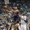 Atlanta Hawks\' Devin Harris (34) goes to the basket as Utah Jazz\'s Earl Watson (11) and Al Jefferson (25) watch during the first quarter of an NBA basketball game Wednesday, Feb. 27, 2013, in Salt Lake City. (AP Photo/Rick Bowmer)