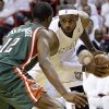 Miami Heat forward LeBron James looks for an open teammate past Milwaukee Bucks forward Luc Richard Mbah a Moute (12) during the first half of Game 2 of the first-round NBA basketball playoff series, Tuesday, April 23, 2013 in Miami. The Heat defeated the Bucks 98-86. (AP Photo/Wilfredo Lee)