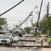 Utility workers try to restore electric power on down lines on Thursday, May 16, 2013, in Cleburne, Texas. A rash of tornadoes slammed into several small communities in North Texas overnight, leaving at least six people dead, dozens more injured and hundreds homeless. The violent spring storm scattered bodies, flattened homes and threw trailers onto cars. (AP Photo/The Dallas Morning News, Michael Ainsworth) MANDATORY CREDIT; MAGS OUT; TV OUT; INTERNET USE BY AP MEMBERS ONLY; NO SALES