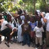 SandRidge Energy worker Jessi Garrett, a senior engineering technician, plays with children in Frettas, Haiti. SandRidge volunteers pay their own way to Haiti but don\'t have to spend their vacation time. - Provided