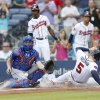 Photo - Atlanta Braves' Freddie Freeman (5) scores on a Chris Johnson three-run double as New York Mets catcher Travis d'Arnaud, second from left, waits for the throw in the first inning of a baseball game in Atlanta, Wednesday, July 2, 2014. (AP Photo/John Bazemore)
