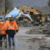 Workers walk through mud as heavy equipment operators work to clear debris Tuesday, March 25, 2014, from Washington Highway 530 on the western edge of the massive mudslide that struck the area Saturday, killing at least 14 people and leaving dozens missing. (AP Photo/Ted S. Warren, Pool)