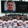 The Boston Red Sox line up during a tribute to victims of the Boston Marathon bombing and its aftermath, as an image of Massachusetts Institute of Technology Police Officer Sean Collier is displayed on the scoreboard, before a baseball game against the Kansas City Royals in Boston, Saturday, April 20, 2013. (AP Photo/Michael Dwyer) ORG XMIT: MAMD125