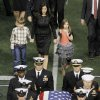 Photo - Christopher Kyle's wife, Taya, and his two children follow behind his casket during the recession of a memorial service for Kyle at Cowboys Stadium, Monday, Feb. 11, 2013, in Arlington, Texas. Thousands attended the public memorial service for Kyle, the former Navy SEAL sniper who was shot to death at a Texas shooting range. (AP Photo/Brandon Wade)