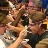 Spoon feeding. One of the tasks to be completed during the J. D. McCarty Center's Amazing Race team building exercise was for two team members to feed each other a bowl of chocolate pudding while blindfolded. Only the team member's knees could be touching for this event. The Amazing Race was the kickoff event for the McCarty Center's month long employee appreciation month. Community Photo By: Greg Gaston Submitted By: Greg,