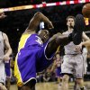 Los Angeles Lakers\' Jodie Meeks, center, loses control of the ball as he drives to the basket against the San Antonio Spurs during the first half of Game 1 of their first-round NBA playoff basketball series, Sunday, April 21, 2013, in San Antonio. (AP Photo/Eric Gay)