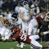 Photo - Connecticut's Zack Frazer is sacked by Oklahoma's Ronnell Lewis during the first quarter of the Fiesta Bowl NCAA college football game Saturday, Jan. 1, 2011, in Glendale, Ariz. (AP Photo/The Courant, John Woike)
