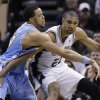 San Antonio Spurs\' Tim Duncan (21) is pressured by Denver Nuggets\' JaVale McGee, center, during the second half of an NBA basketball game, Wednesday, March 27, 2013, in San Antonio. San Antonio won 100-99. (AP Photo/Eric Gay)