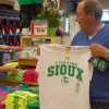 FILE - In this, Tuesday, June 12, 2012, file photo, Buck Striebel holds up a University of North Dakota Fighting Sioux T-shirt while his wife, GaeLynn, sorts through other shirts on sale at a sporting goods store in Bismarck, N.D. The decades-old debate over whether to keep the University of North Dakota\'s Fighting Sioux nickname finally seemed to come to an end as 68 percent of voters in the June primary agreed it was time to drop the nickname deemed