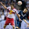 Photo - New York Red Bulls' Eric Alexander, left, and Vancouver Whitecaps' Jordan Harvey vie for the ball during first half MLS soccer action in Vancouver, B.C., on Saturday March 8, 2014. (AP Photo/The Canadian Press, Darryl Dyck)