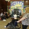 Photo - In this Tuesday, Jan. 8, 2013 photo, caregiver Kim Bauer, right, pauses as the elderly woman she is helping looks at a decorative fireplace at Cedar Village retirement community, in Mason, Ohio. The woman she is helping has suffered abuse by a relative. The Shalom Center that is a part of the community helps the woman by offering shelter, along with medical, psychological and legal help, to elderly abuse victims in this northern Cincinnati suburb. The center asked that her identity be protected for this story because the close relatives who allegedly abused her don't know where she is. (AP Photo/Al Behrman)