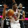 Chicago Bulls shooting guard Jimmy Butler (21) passes in front of San Antonio Spurs power forward Tim Duncan, left, and small forward Kawhi Leonard, right, during the second half of an NBA basketball game on Tuesday, March 11, 2014, in Chicago. (AP Photo/Andrew A. Nelles)