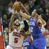 Photo - Chicago Bulls forward Carlos Boozer (5) battles for a rebound against Philadelphia 76ers forward Evan Turner (12) during the first half of an NBA basketball game in Chicago, Saturday, Jan. 18, 2014. (AP Photo/Nam Y. Huh)