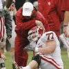 Trainers check out an injury to offensive lineman Stephen Good (77) during the spring Red and White football game for the University of Oklahoma (OU) Sooners at Gaylord Family/Oklahoma Memorial Stadium on Saturday, April 17, 2010, in Norman, Okla. Photo by Steve Sisney, The Oklahoman