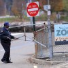 Photo -   A security guard closes the gate at the Pittsburgh Zoo, where zoo officials say a young boy was killed after he fell into the exhibit that was home to a pack of African painted dogs, who pounced on the boy and mauled him, Sunday, Nov. 4, 2012. It's not clear whether he died from the fall or the attack, said Barbara Baker, president and CEO of the Pittsburgh Zoo & PPG Aquarium. (AP Photo/John Heller)