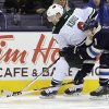 Photo - Minnesota Wild's Mikko Koivu, left, of Finland, and Columbus Blue Jackets' Matt Calvert chase a loose puck during the first period of an NHL hockey game on Friday, Dec. 6, 2013, in Columbus, Ohio. (AP Photo/Jay LaPrete)