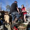 Clint Lowery, left, and Amanda Lowery, right, remove a deep fryer from the family\'s tornado damaged mobile home in Century, Fla., Tuesday, Feb. 16, 2016. (AP Photo/Michael Snyder)